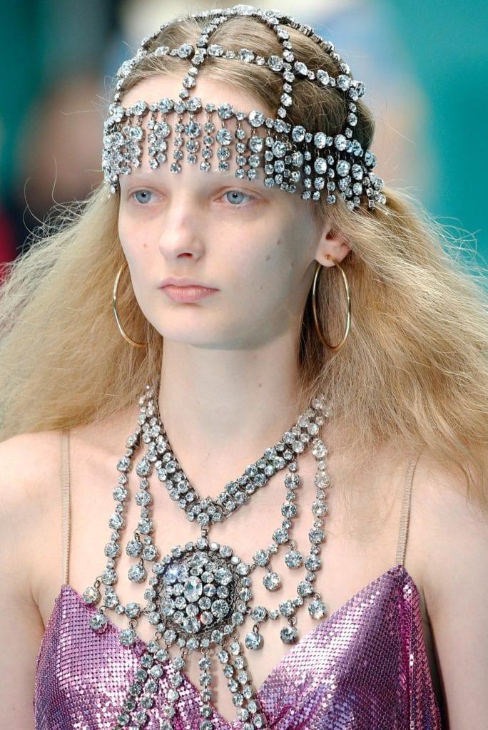Mujer rubia de cabello suelto -parece algo frizzado- con una semi corona de strass