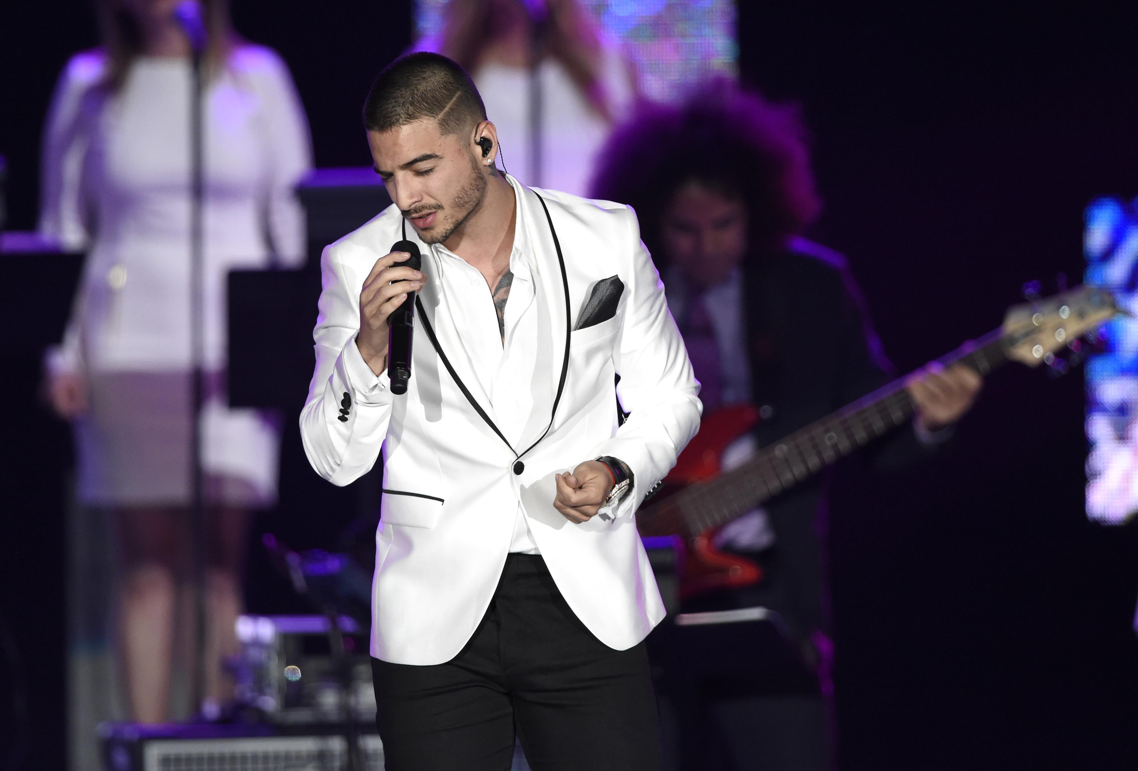 Maluma en el escenario con cabello rapado, morocho