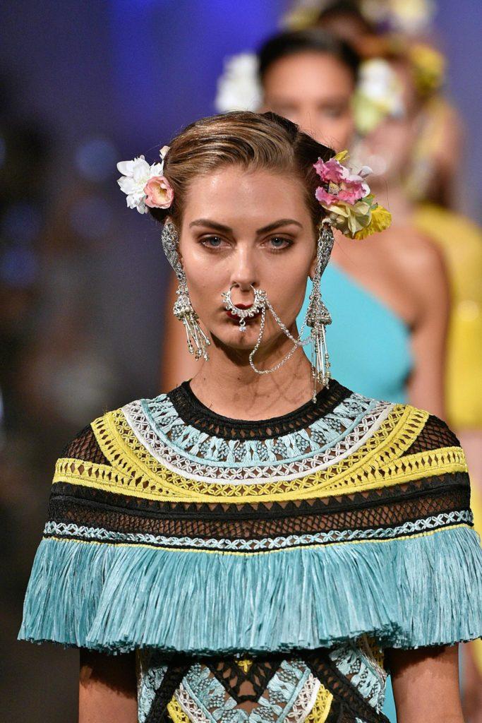 Mujer con cabello atado y tocados florales a los costados