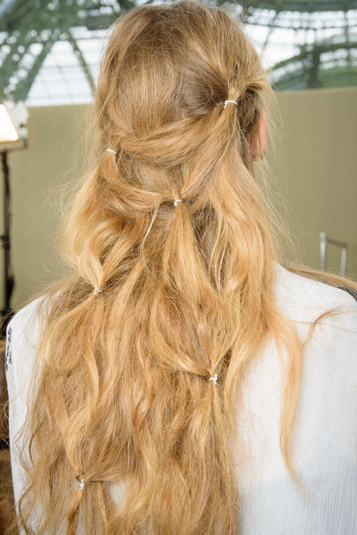 Mujer de espaldas, rubia, cabello suelto con pequeñas hebillas a modo decorativo