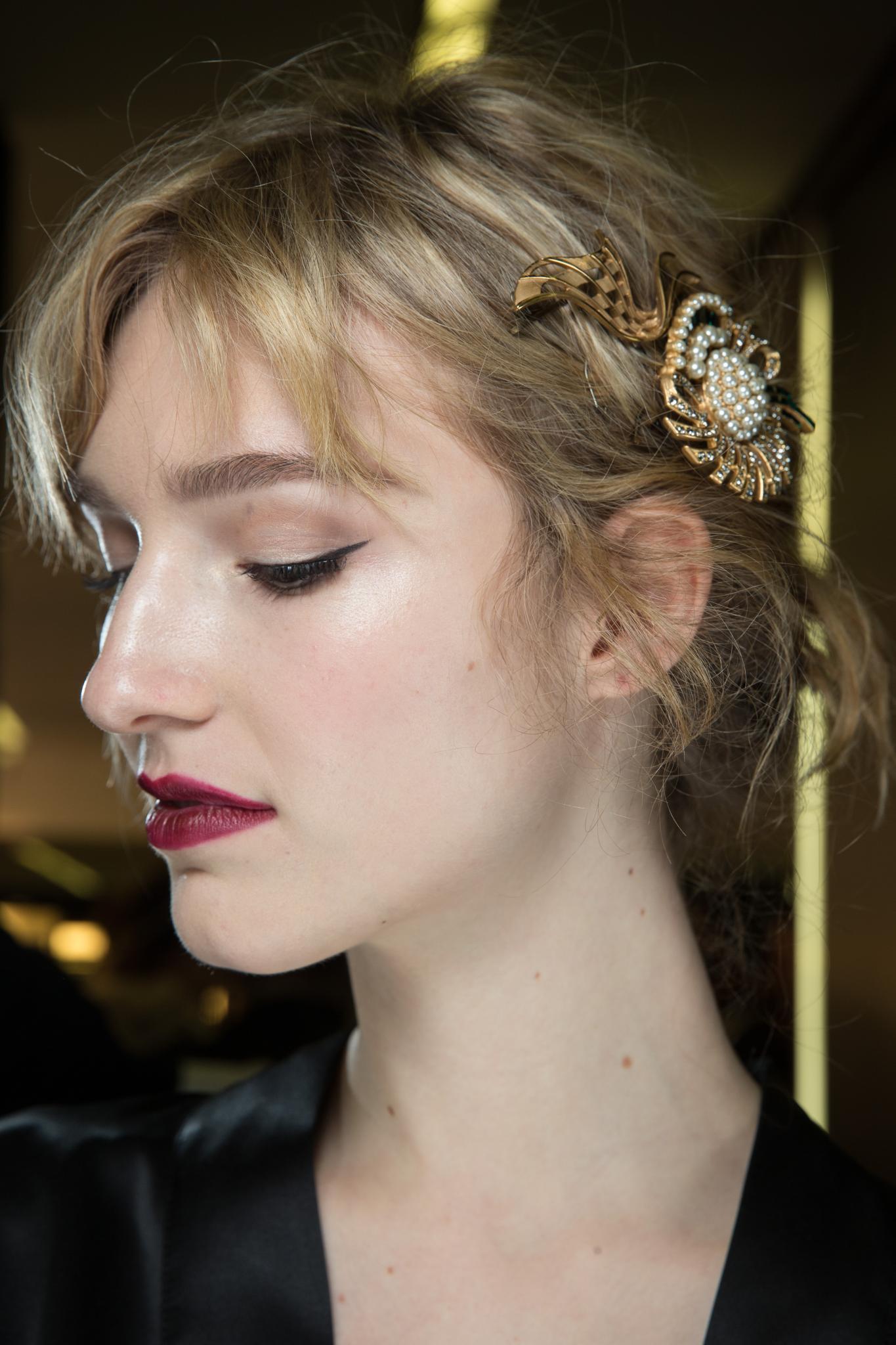 Mujer rubia, cabello corto con flequillo, lleva un aplique de costado