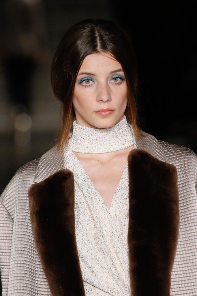 Mujer de cabello castaño rojizo, con raya al medio. Lo lleva atado con dos mechones que le caen a los costados del rostro.
