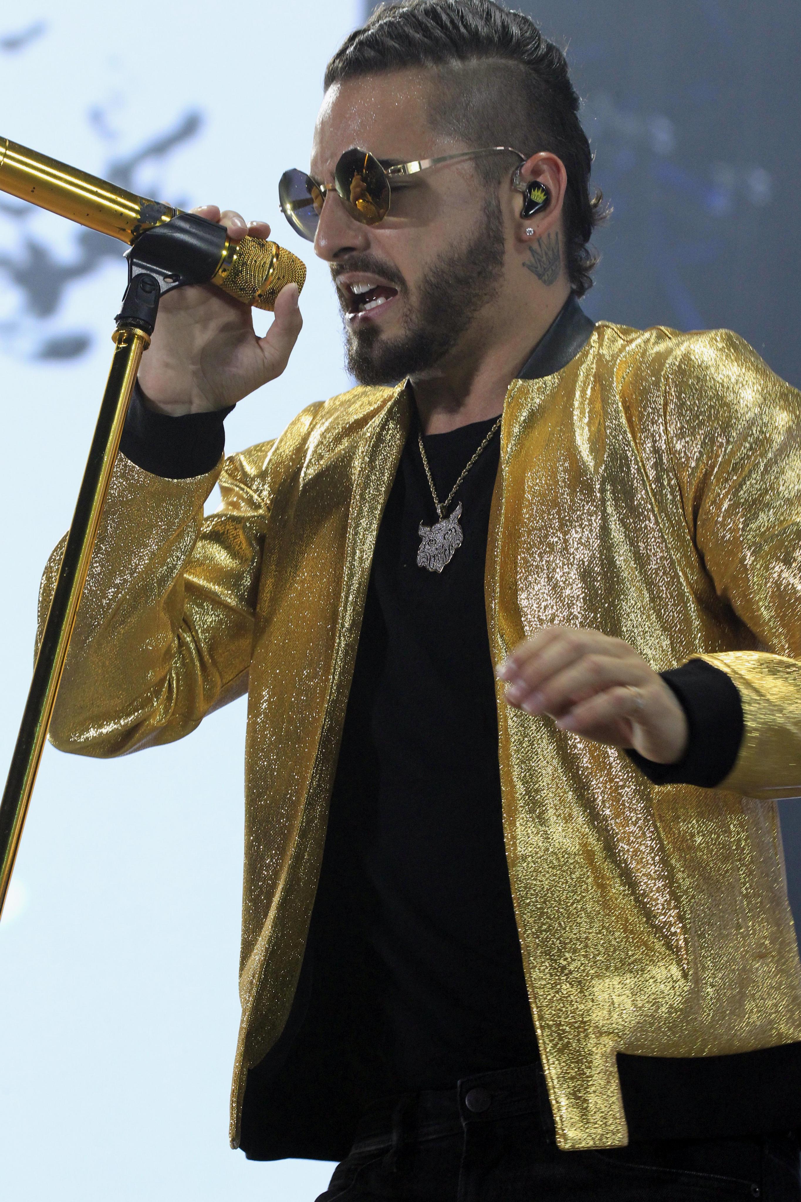 Maluma cantando, visto de perfil, lleva rapado uno de los lados y una cresta en el medio. Castaño oscuro.