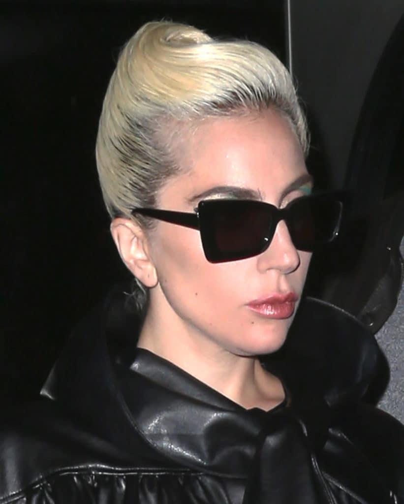 Mujer rubia de raíces negras, cabello recogido hacia un costado, estilo elegante