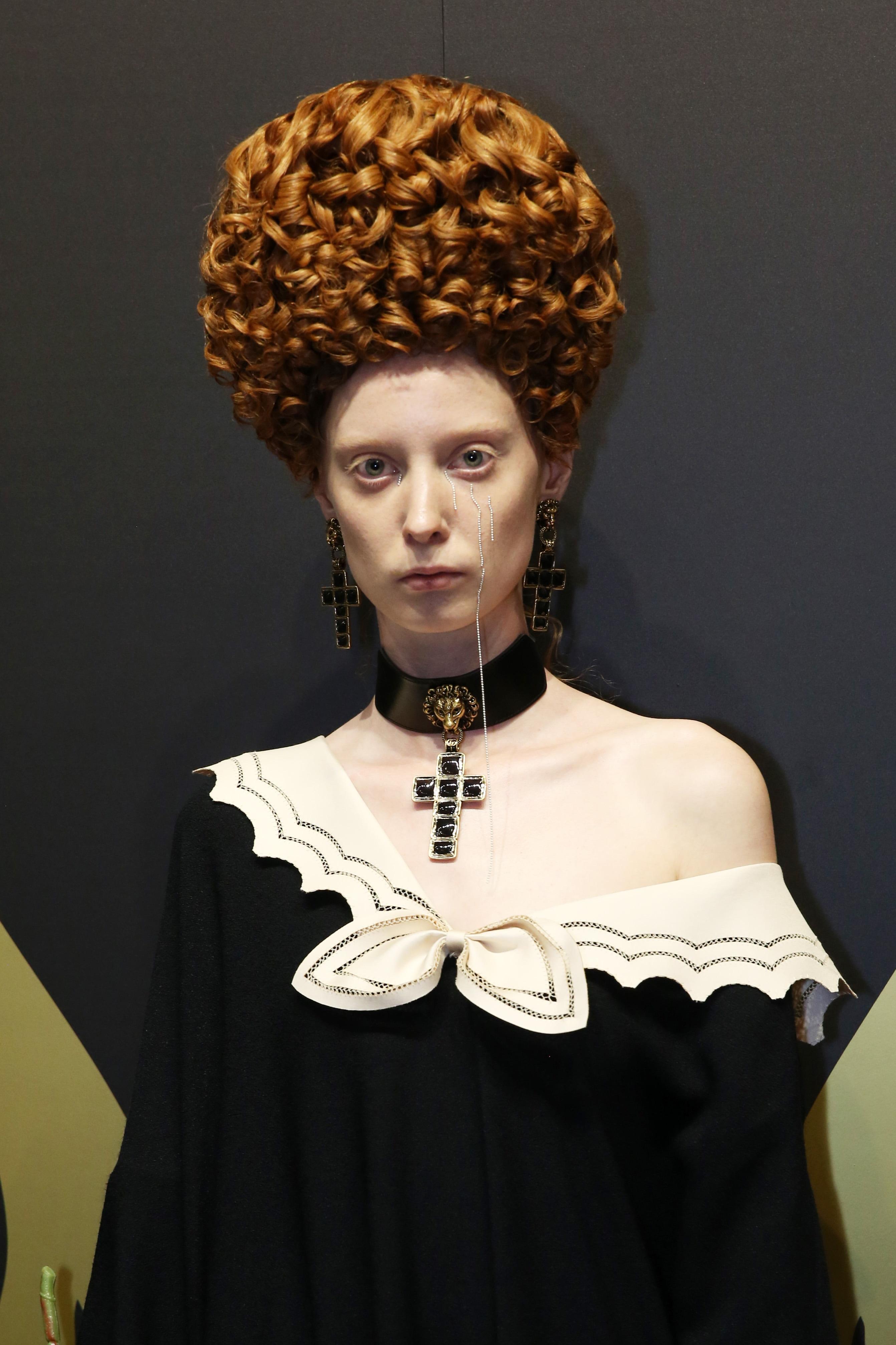 Mujer de cabello castaño cobrizo, lleva un gran rodete sobre su cabeza formado por trenzas. Look dramático y teatral.