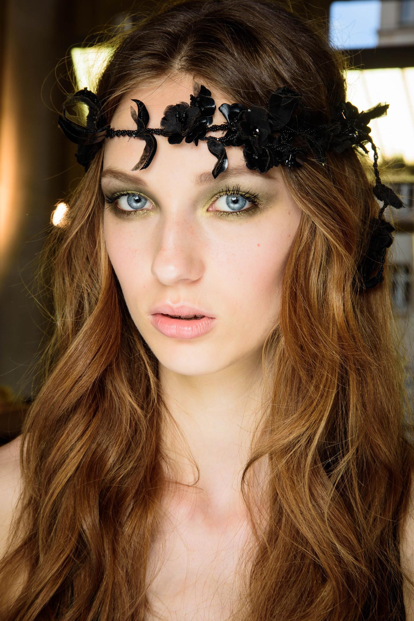 Cabello suelto, ondulado, castaño rojizo con raya al medio y vincha de flores negras
