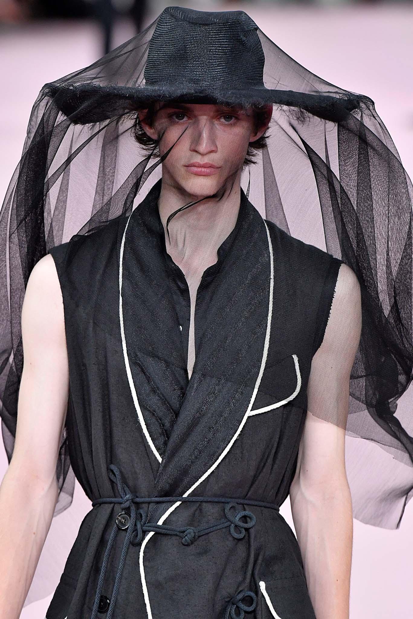 Hombre con sombrero negro de paja y tocado negro de tul