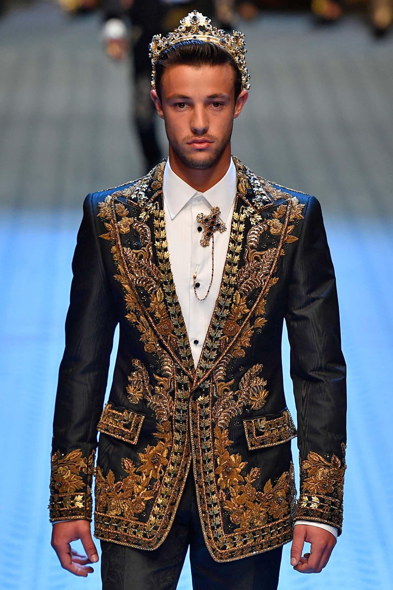 Hombre de cabello corto castaño peinado hacia atrás con corona