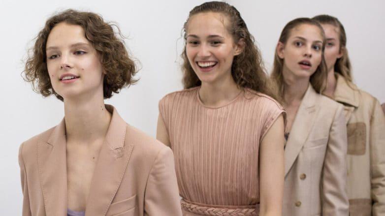 Cuatro mujeres desfilando, la primera, cuyo rostro es más visible, lleva el cabello corto con rulos y sin raya