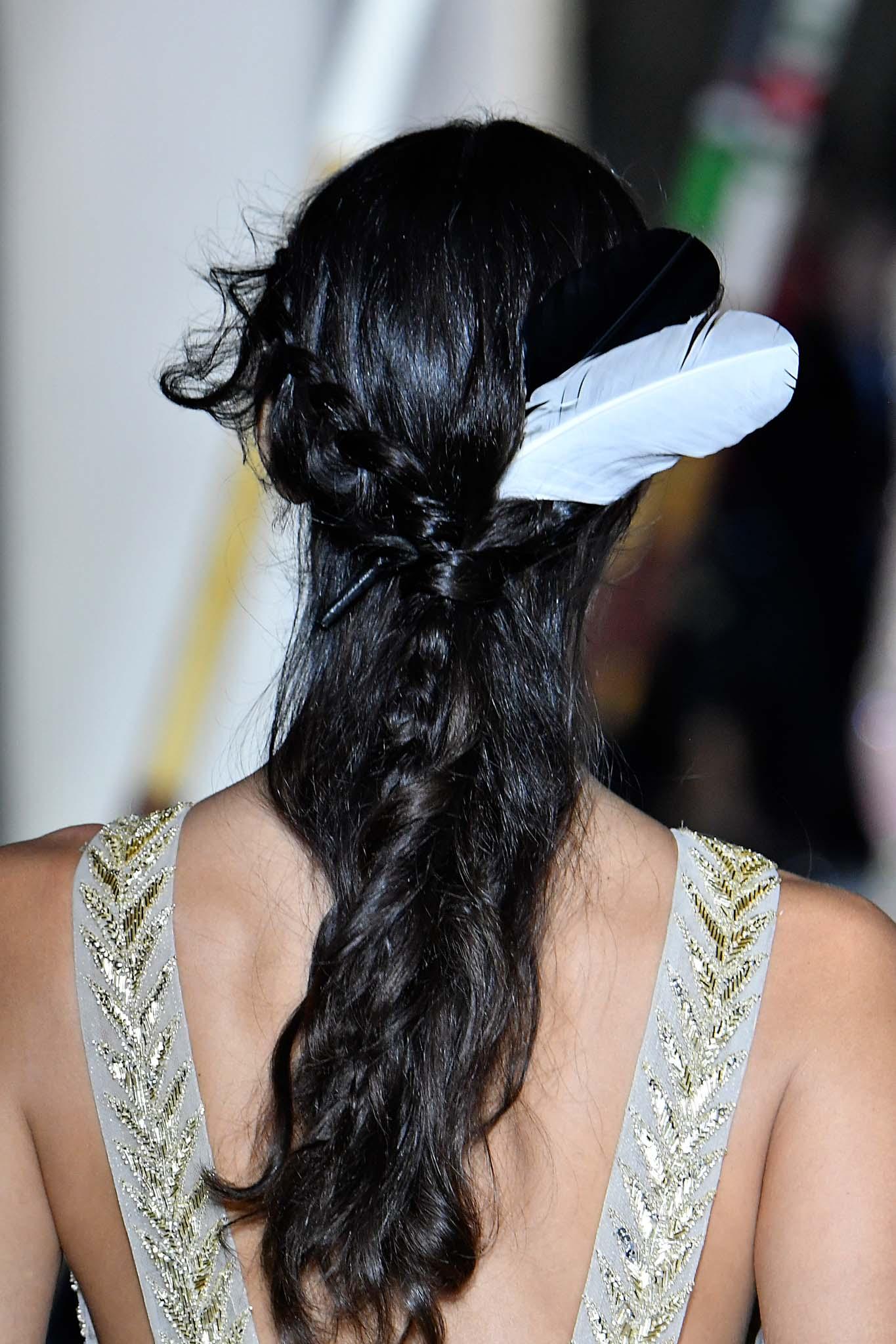 Vista desde atrás de cabellera negra, peiando semirecogido con una pluma blanca