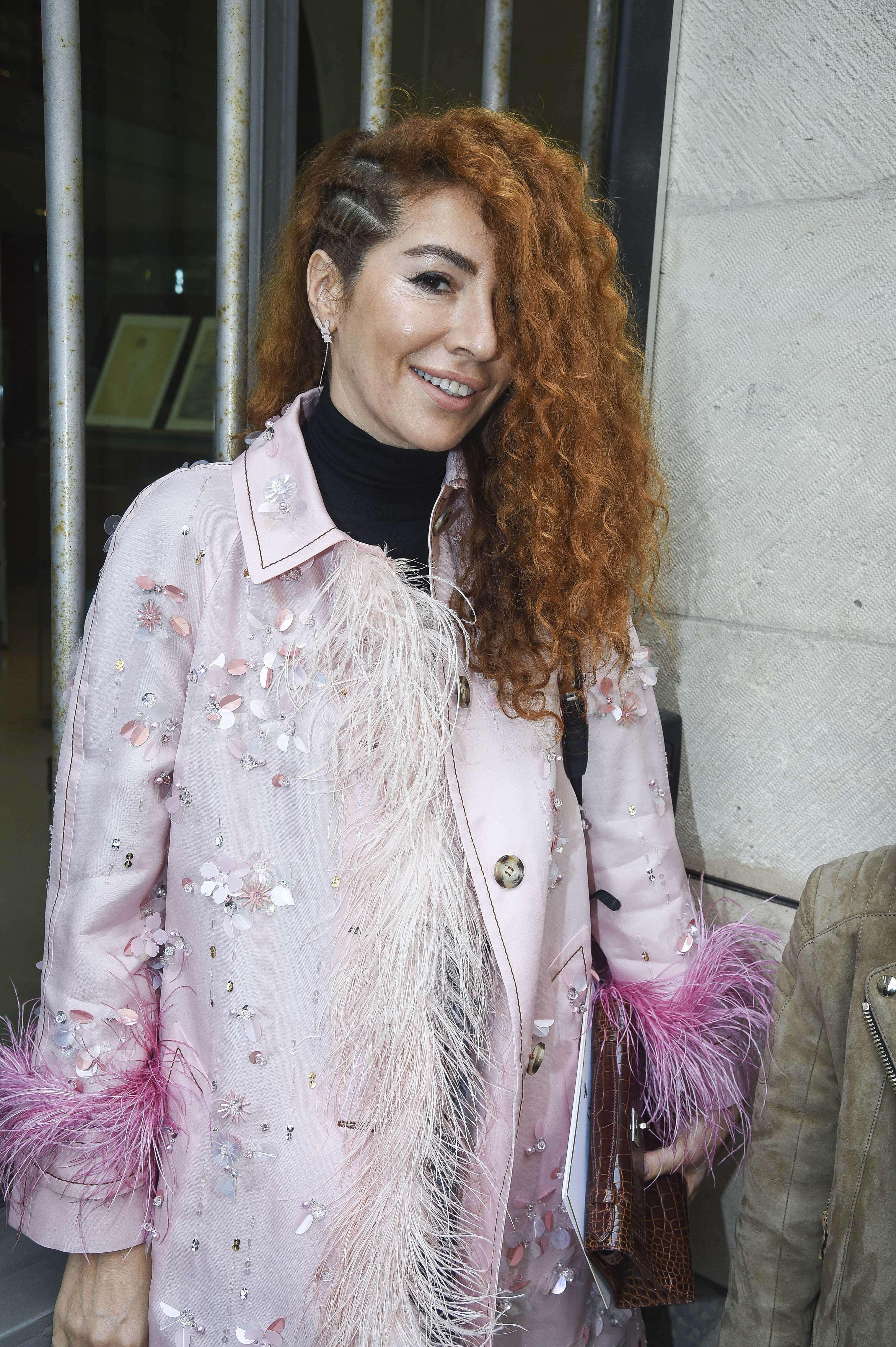 Mujer de melena enrulada, colorada, con cabello rapado de un costado y rulos del otro