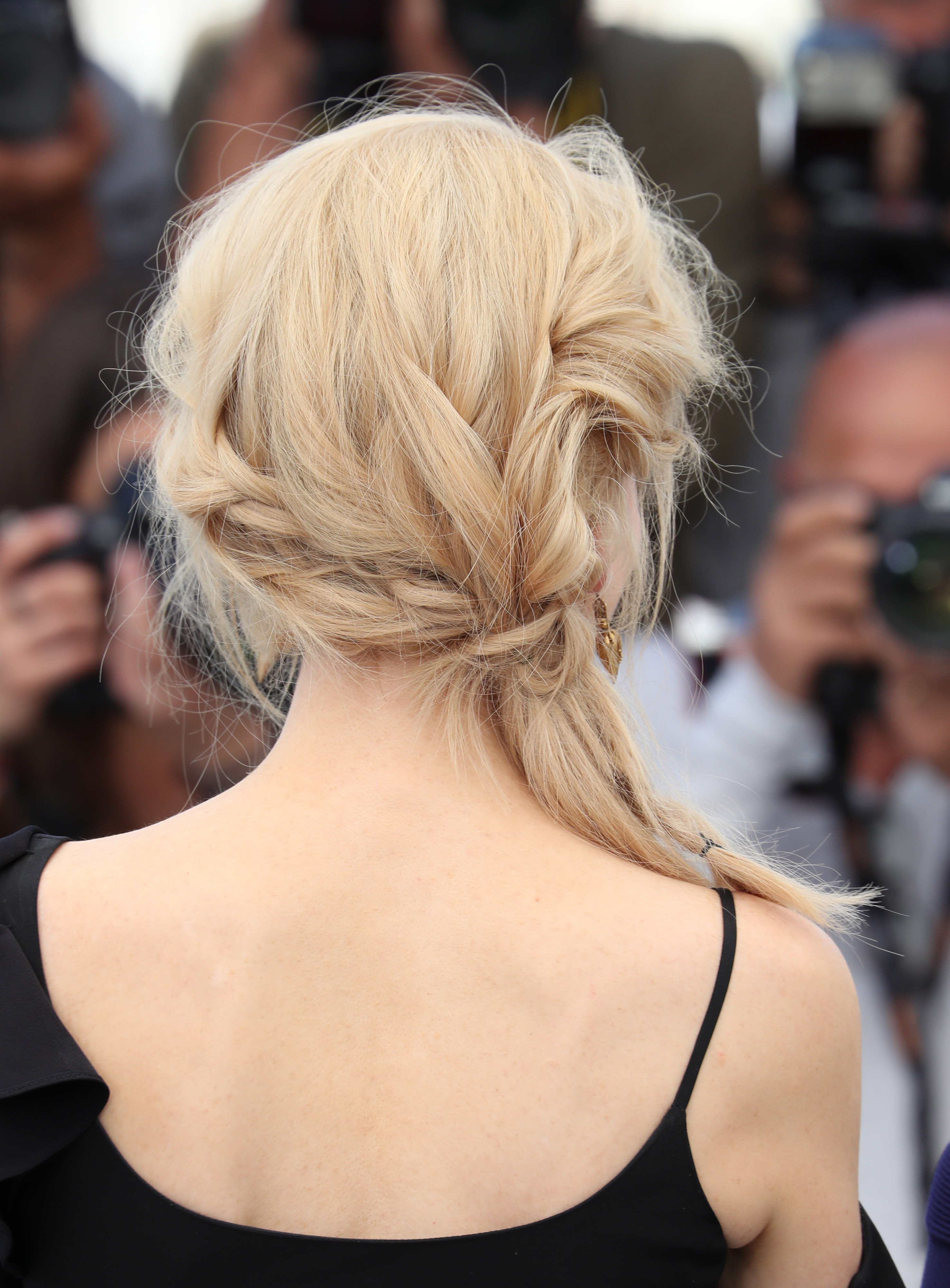 Vista de atrás de cabello rubio recogido en una especie de trenza/coleta