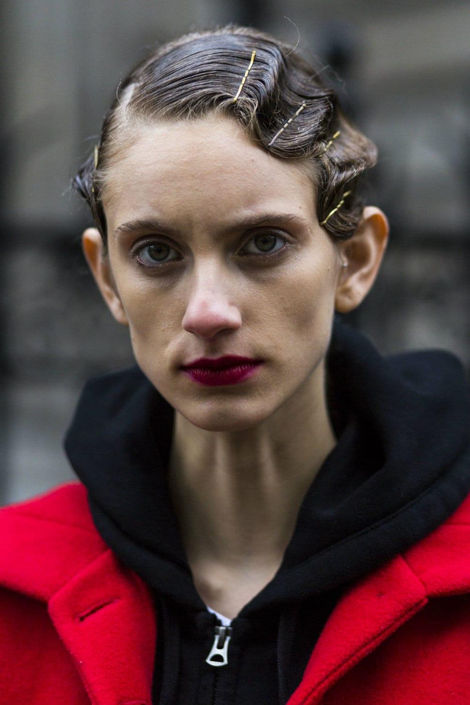 Mujer peinada con gel, el cabello luce fijo, pegado a la cabeza, con forma de hondas, sostenido por hebillas metálicas