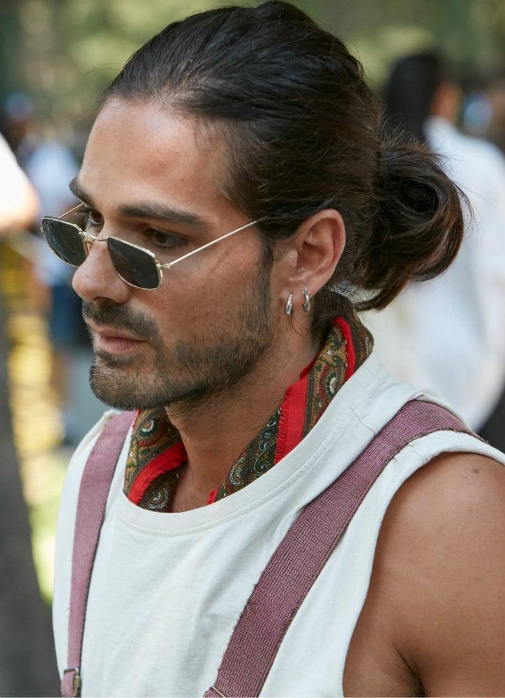 Hombre de cabello lacio, castaño, peinado hacia atrás con coleta