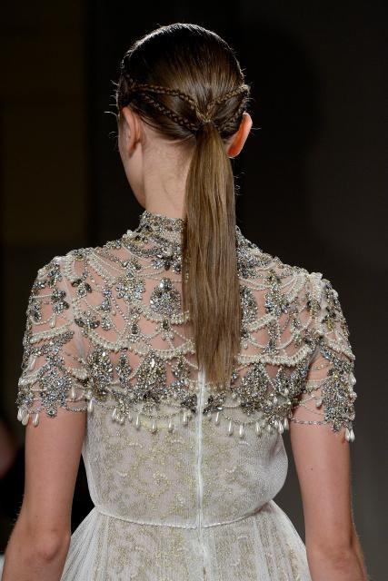 Vista de atrás de mujer peinada con coleta y tres pequeñas trenzas que desmebocan en ella