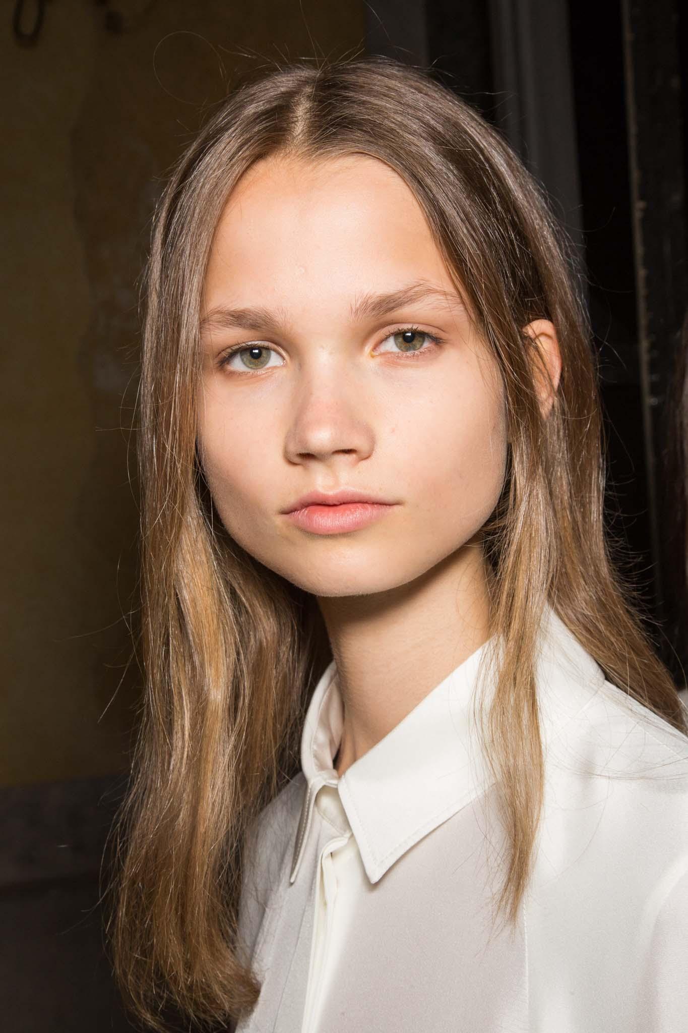 Mujer joven con cabello suelto, castaño, lacio peinado con raya al medio