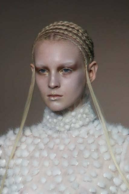 Mujer rubia con el pelo atado en cuatro trenzas que le zurcan la cabeza de un lado hacia el otro