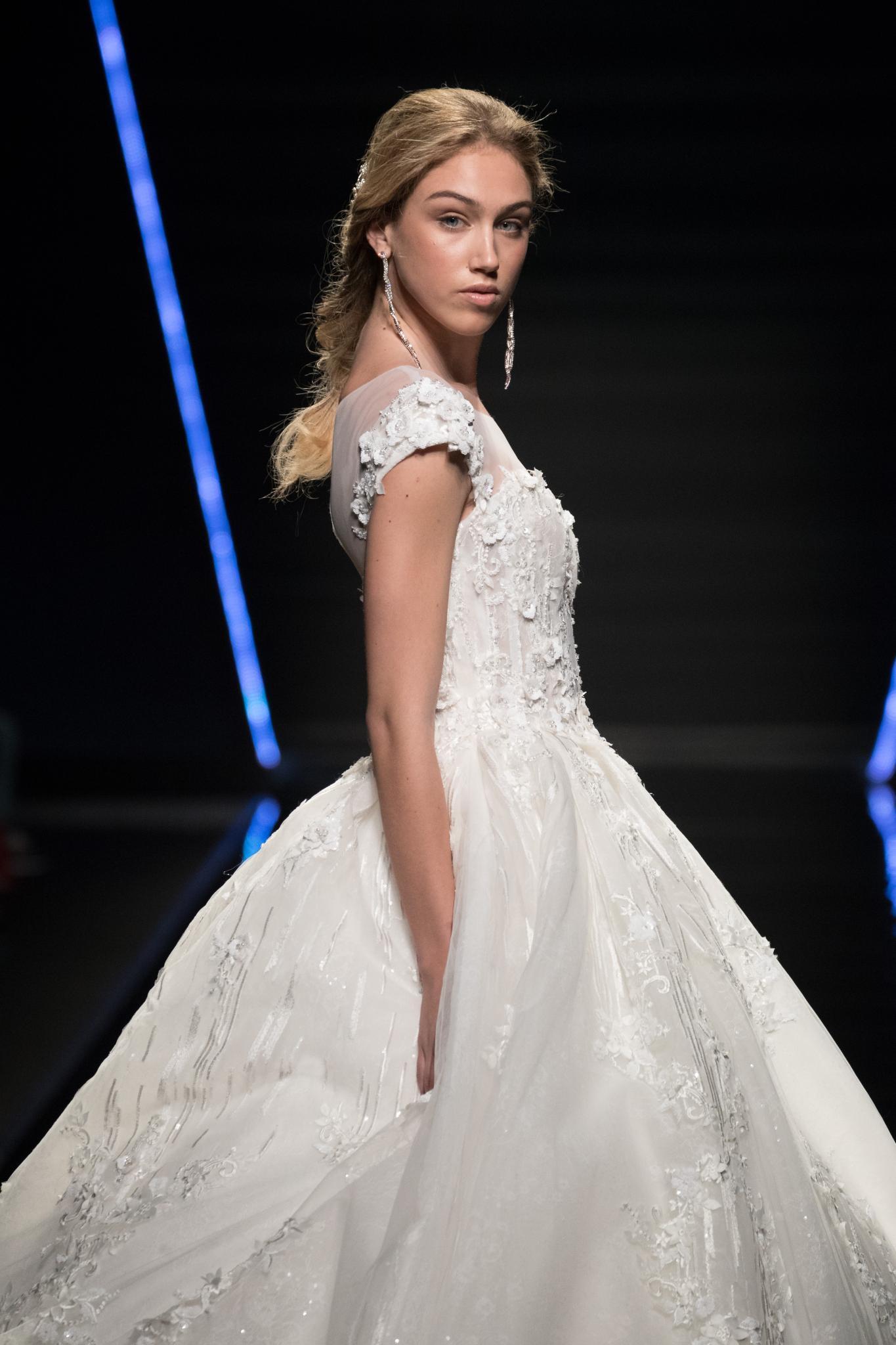 Mujer rubia con cabello semi recogido, parece peinada y vestida como novia