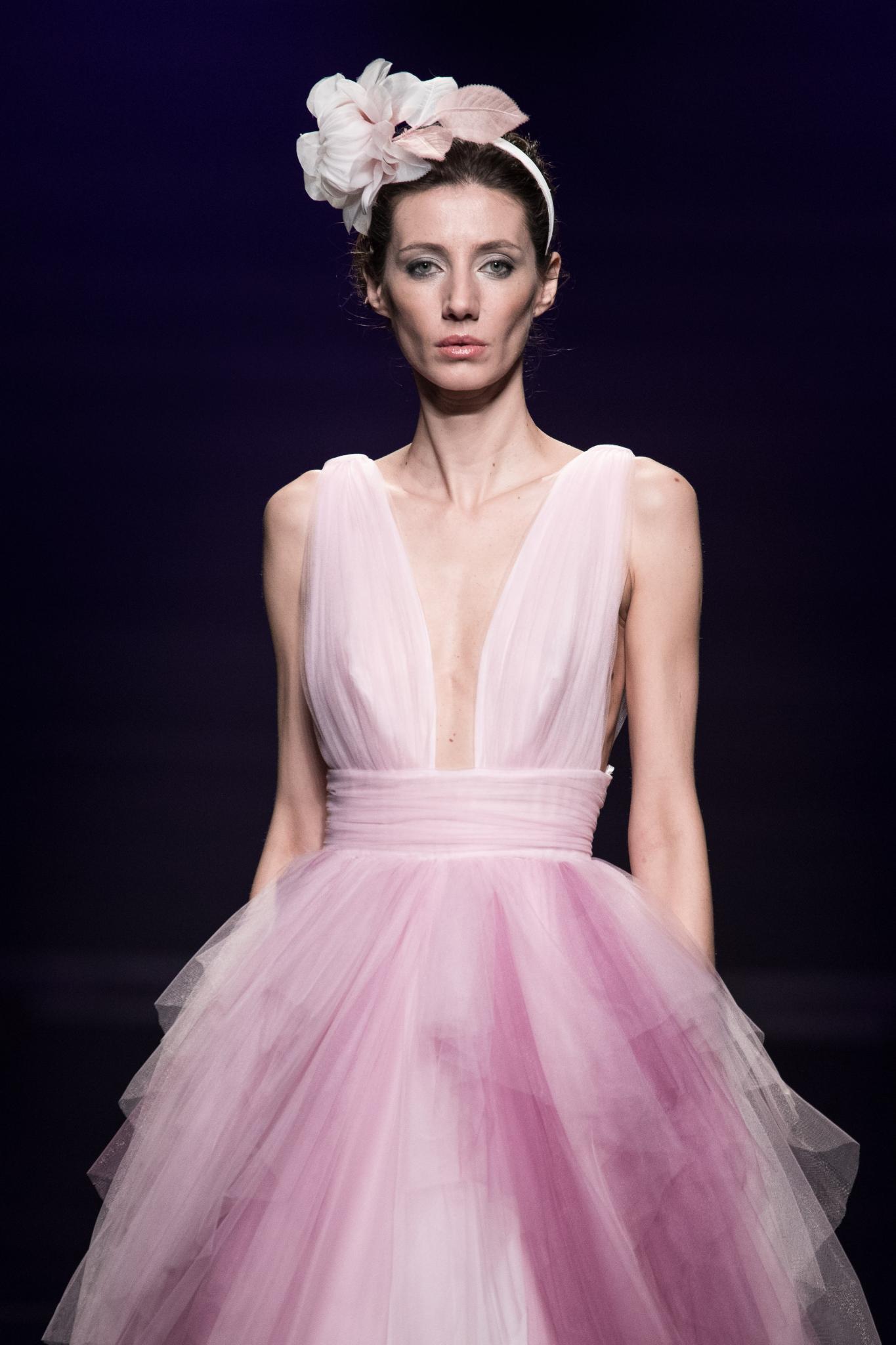 Mujer castaña con cabello totalmente recogido y cubierto por un fascinator de gran tamaño en color rosa
