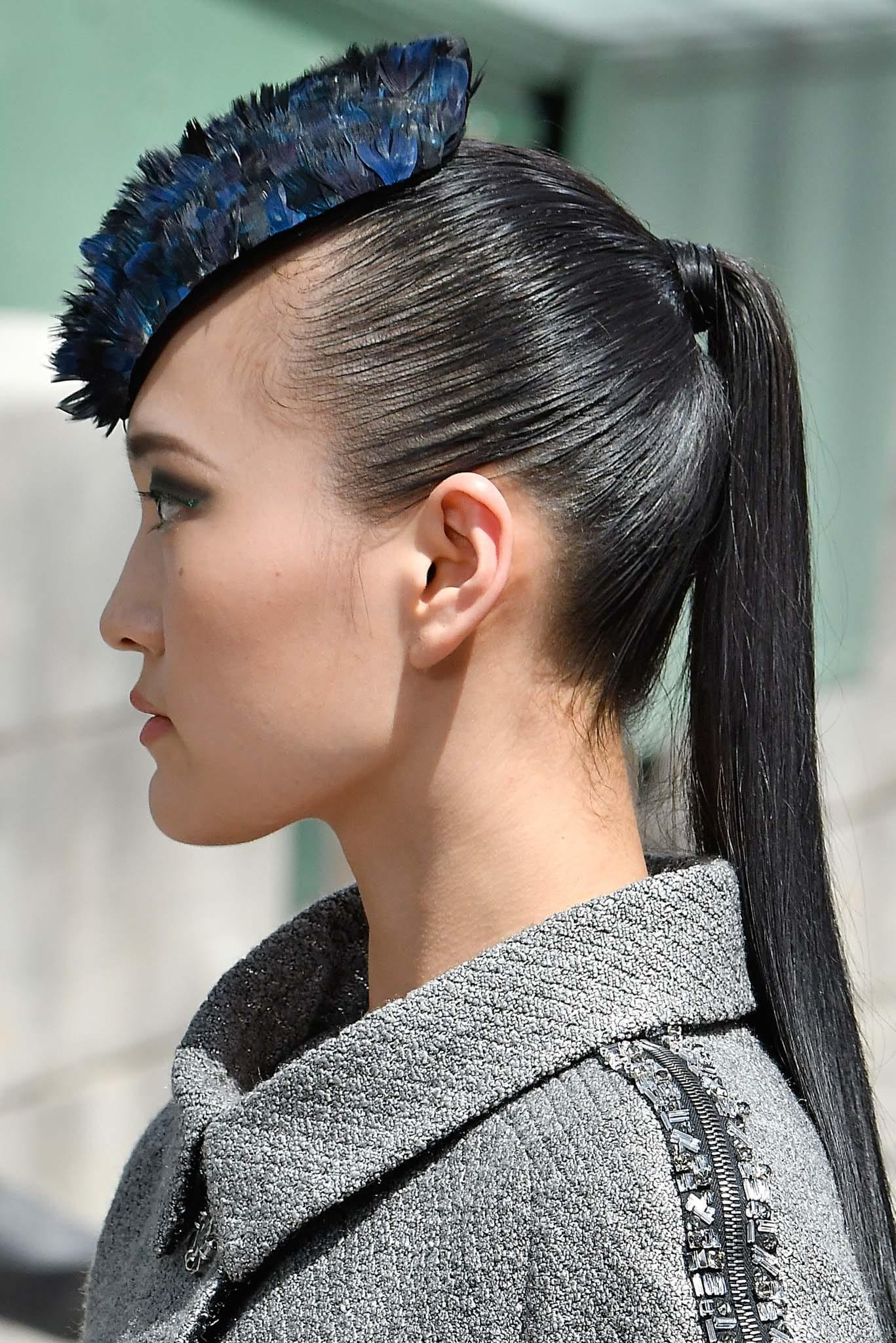 Mujer de cabello oscuro, con pony tail y aplique azul al frente