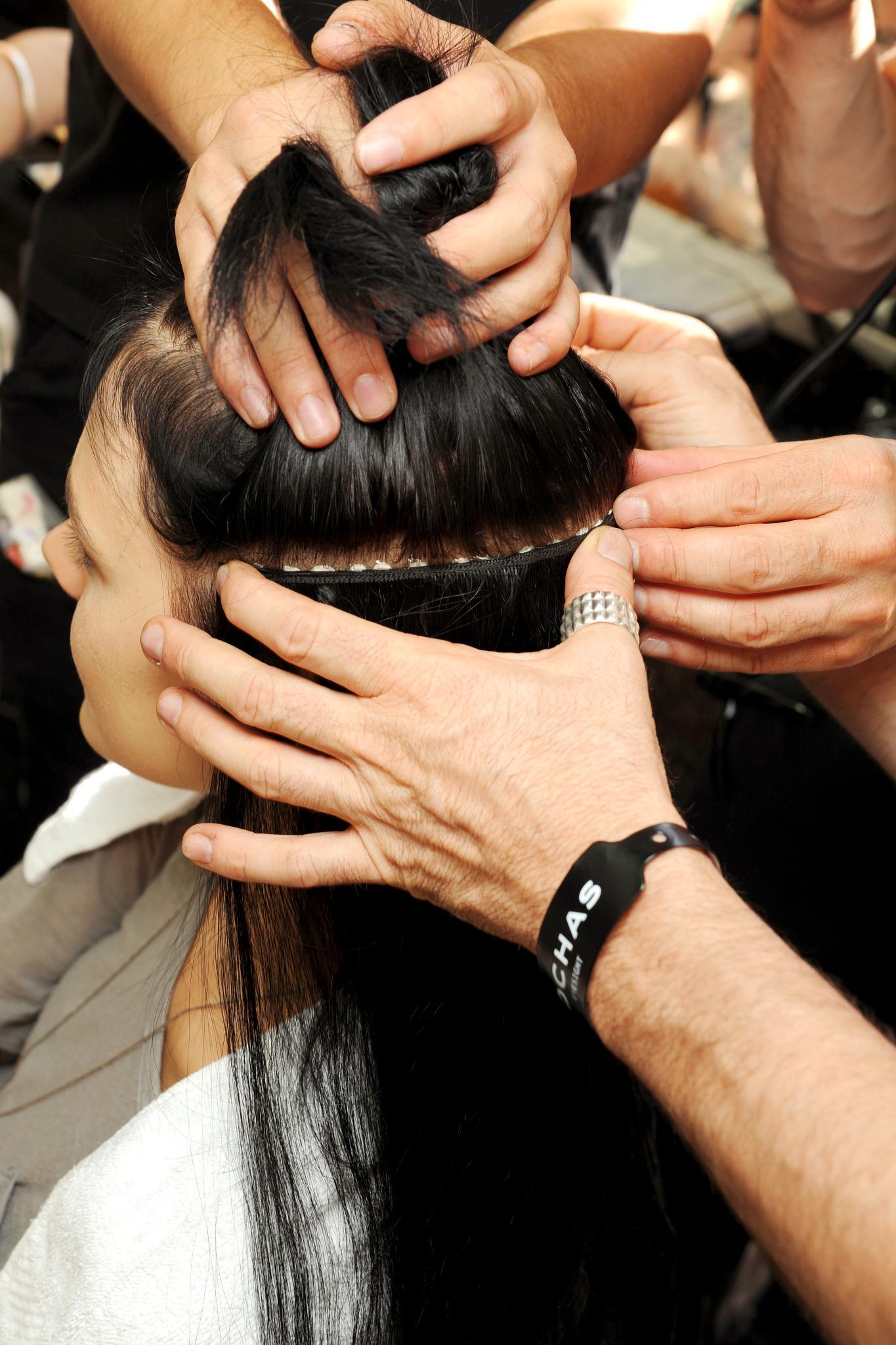 Backstage de peinado, varias manos sostienen una melena lacia y morocha