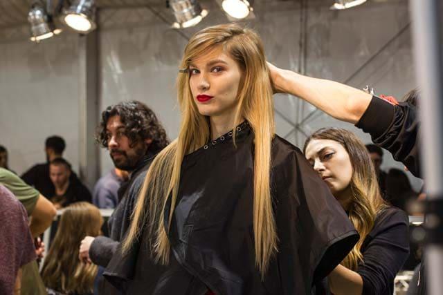 Backstage de peinado de mujer rubia, cabello extra largo, un broche le sostiene parte del pelo