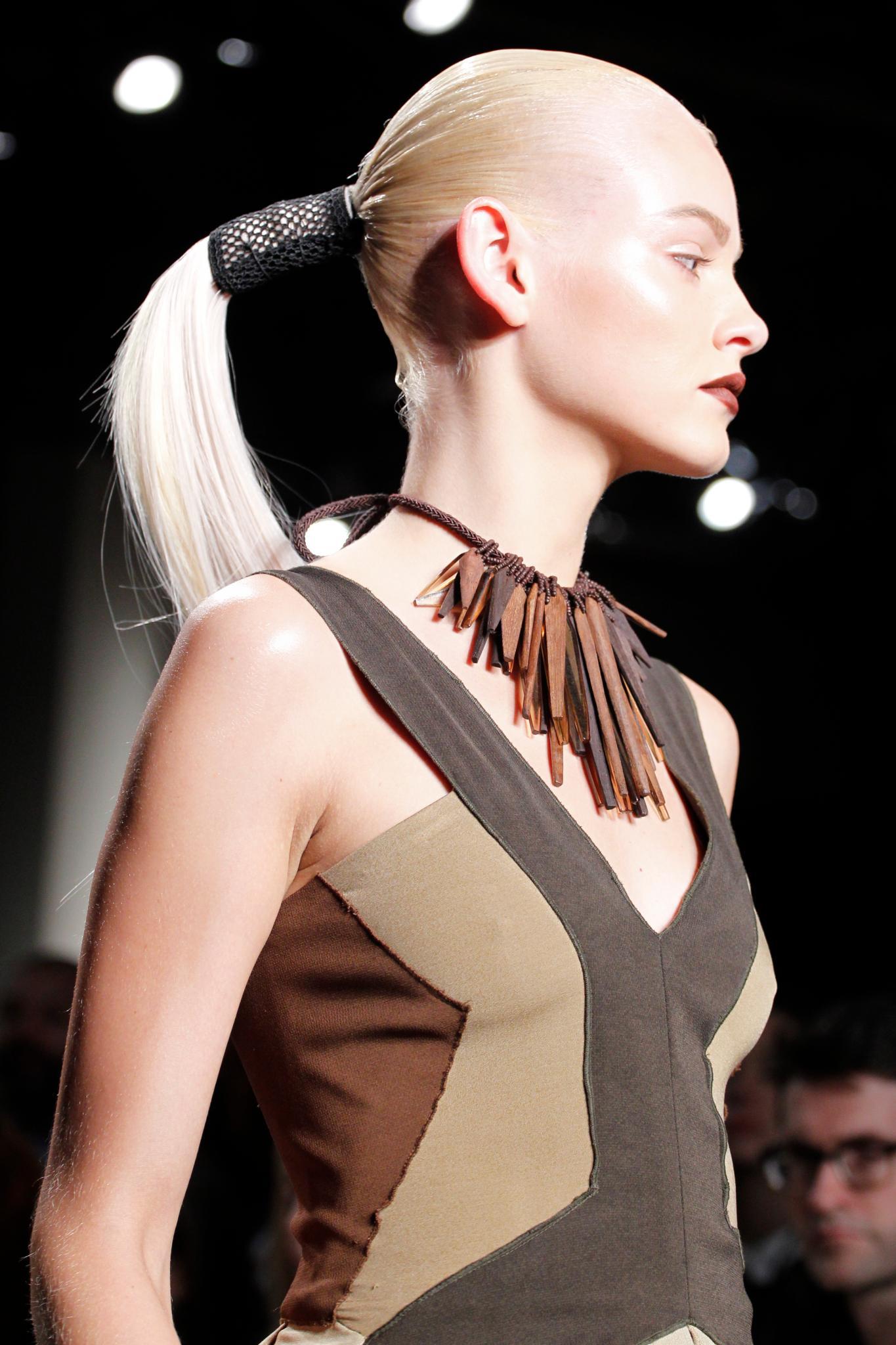 Vista de costado de mujer rubia platinada peinada hacia atrás con pony tail baja