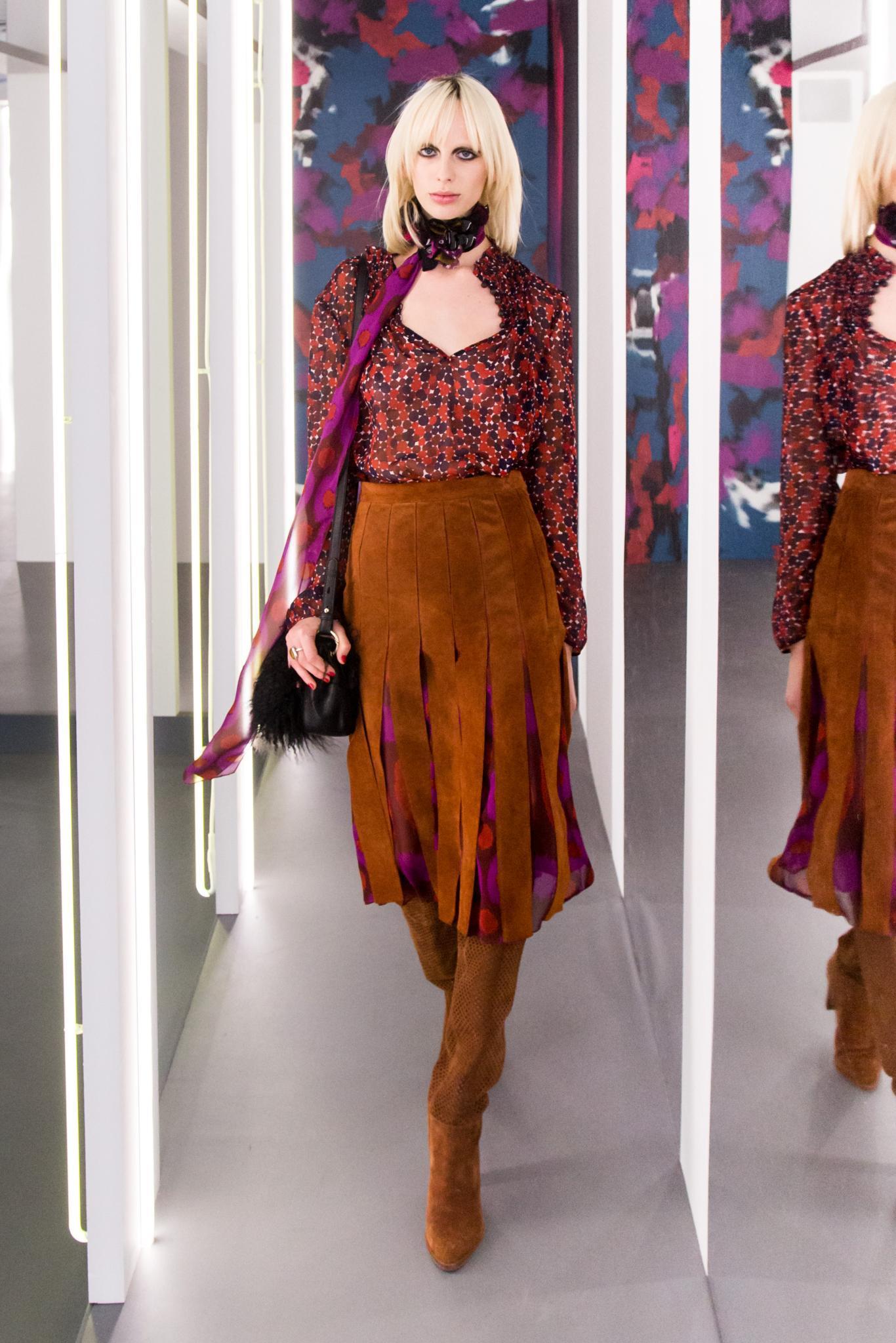 Mujer rubia platinada con raices oscuras, lleva el cabello lacio a la altura de los hombros con raya al medio