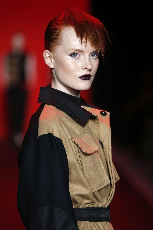 Mujer de cabello ultra corto, rapado a los costados con cresta en el medio y teñida de rojo furioso