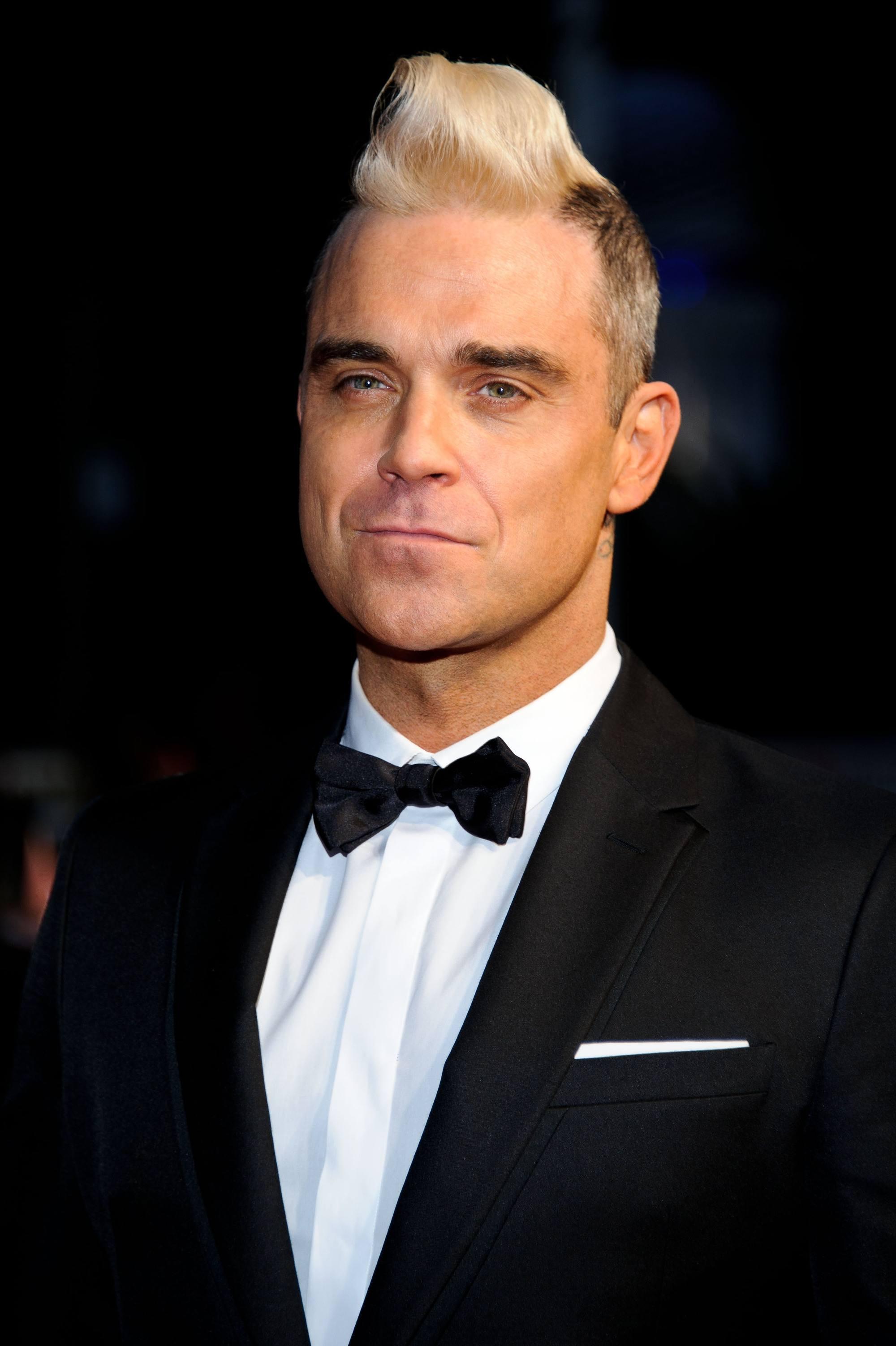 Robbie Williams teñido de rubio platinado, rapado a los costados con jopo alto en el medio