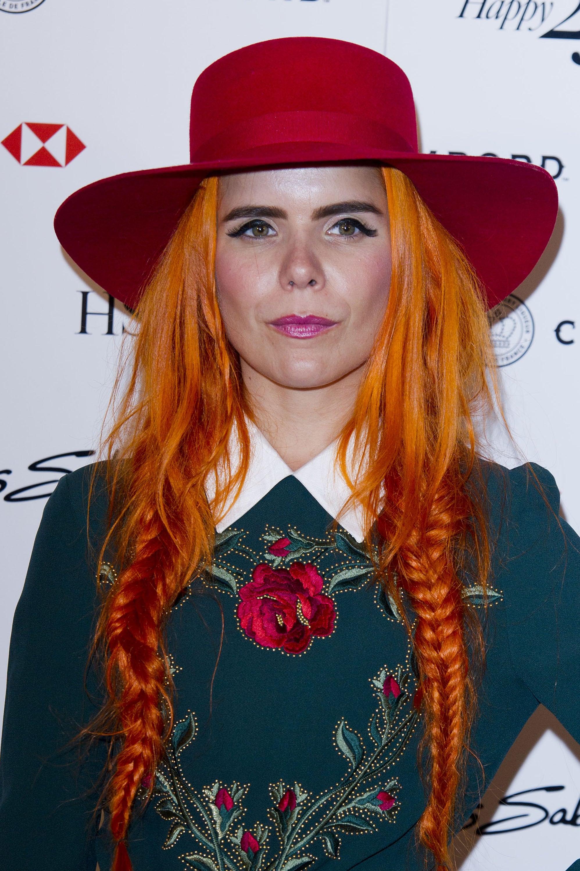 Melena naranja, larga, peinada con dos trenzas y cubierta por un sombrero de ala ancha rojo
