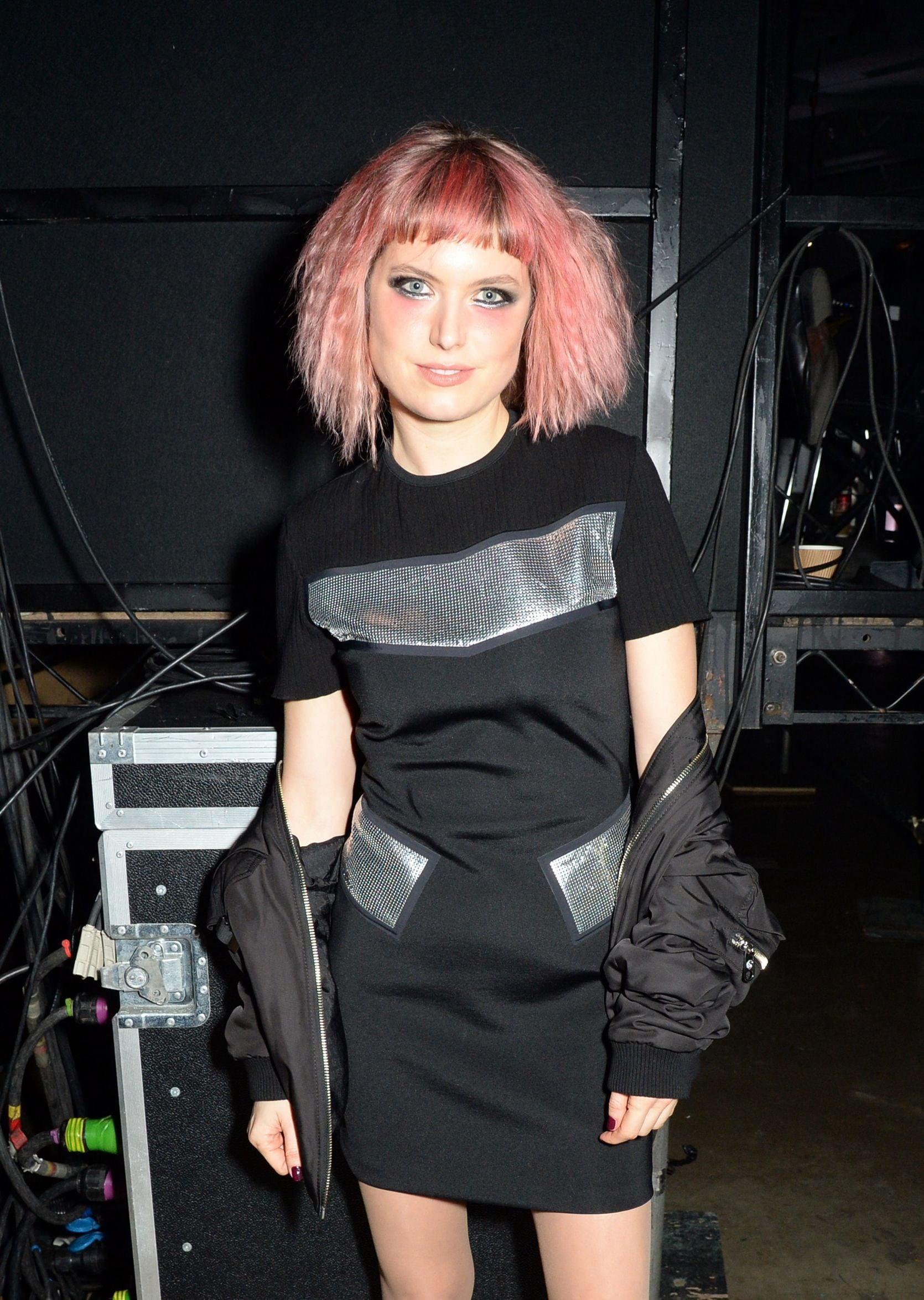 Mujer con cabello frizado sobre los hombros, lleva el flequillo lacio y está teñida de rosa