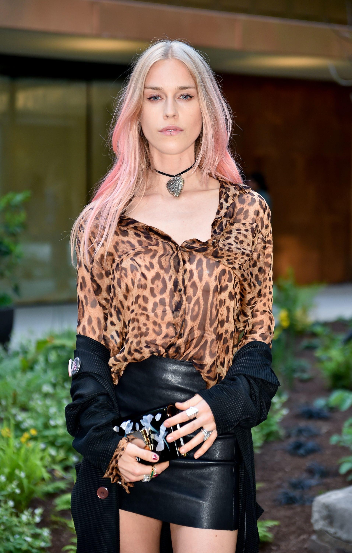 Mujer de melena lacia con movimiento, el cabello es rubio, pero rosa en las puntas. Lleva raya al medio