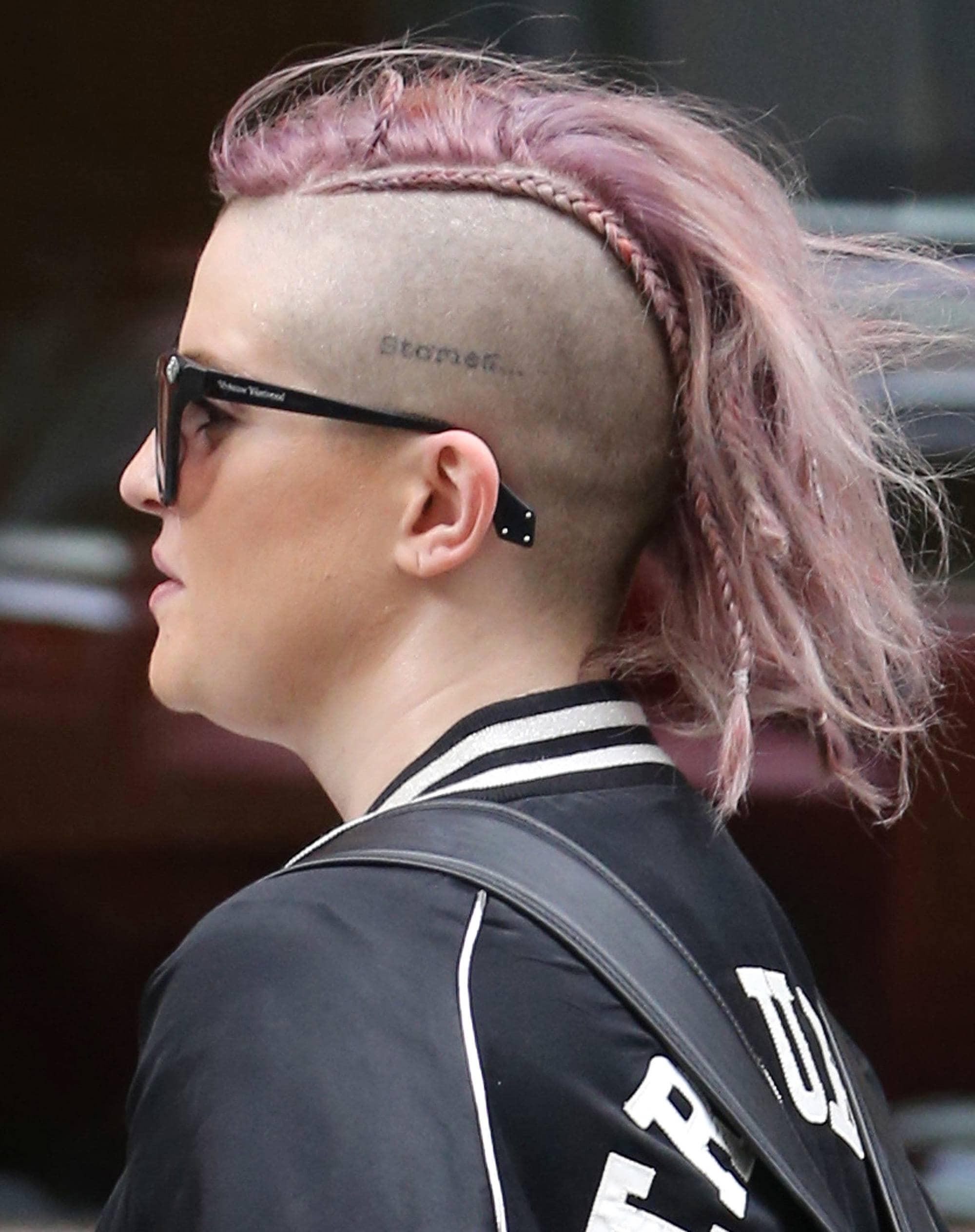 Mujer de cabello rapado a los costados (de un lado lleva un tatuaje) en el medio una cresta rosa alborotada