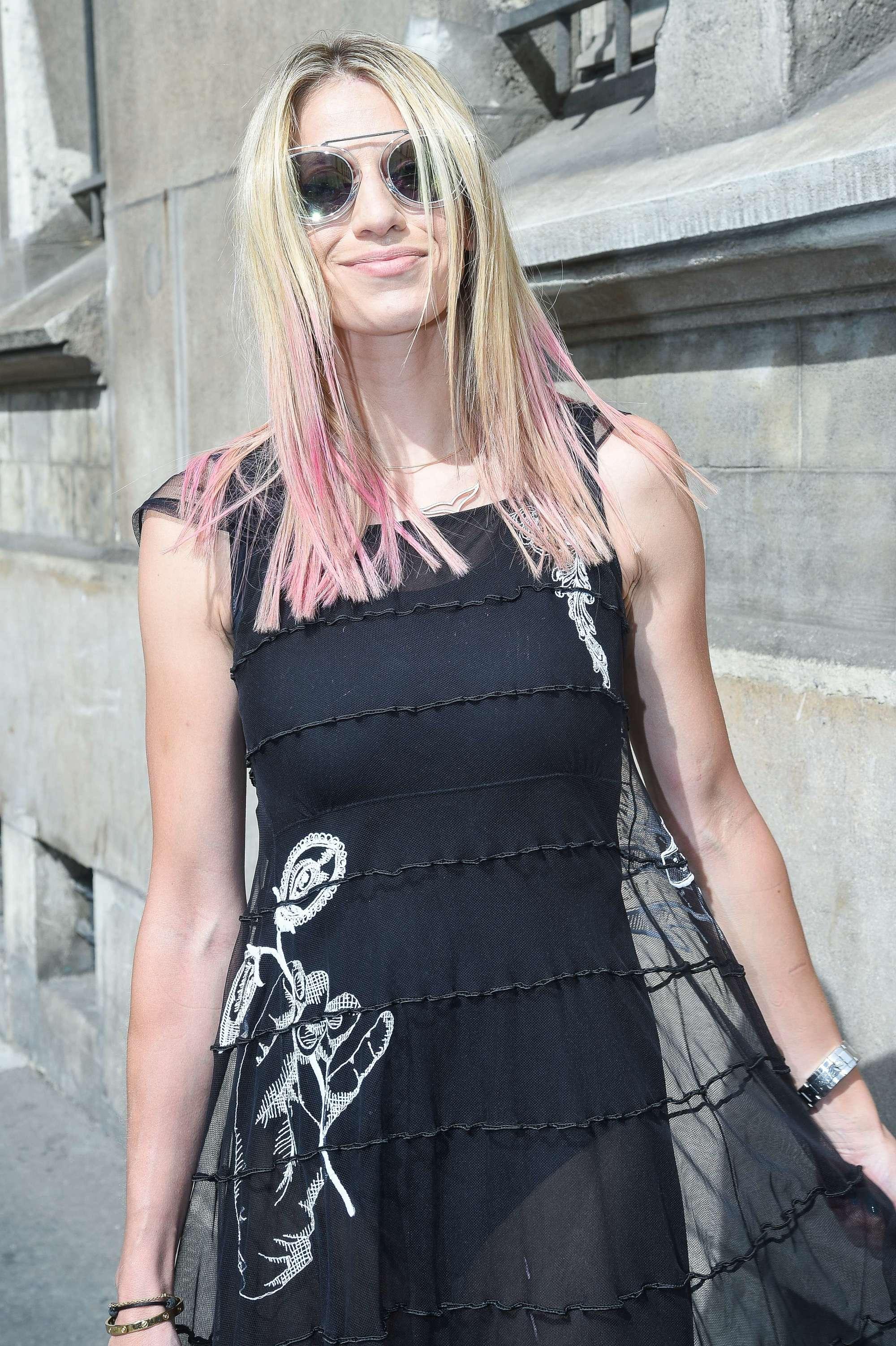 Mujer con melena rubia y raices oscuras, lleva el cabello lacio natural con las puntas rosas y raya al medio.