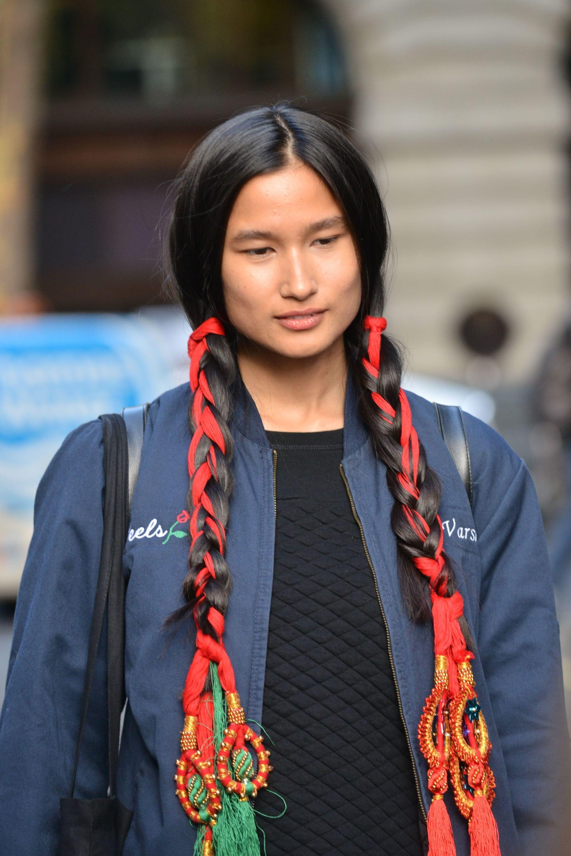 Mujer de melena larga, negra, peinada con raya al costado y dos trenzas hechas con cabello y cintas de colores