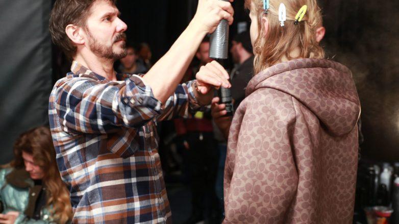 Backstage de peinado, el peluquero, parado, rocía spray sobre el cabello de la modelo