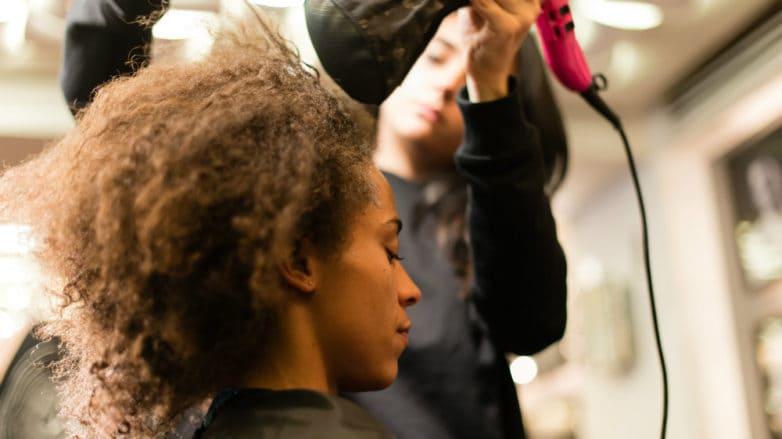 Backstage de peinado: mujer de cabello afro a la que peinan con secador