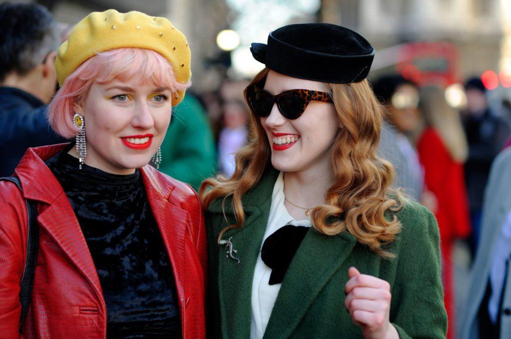 Dos mujeres, una de cabello rosa, carre con gorro; y otra de cabello castaño rojizo, suelto, ondulado y con sombrero