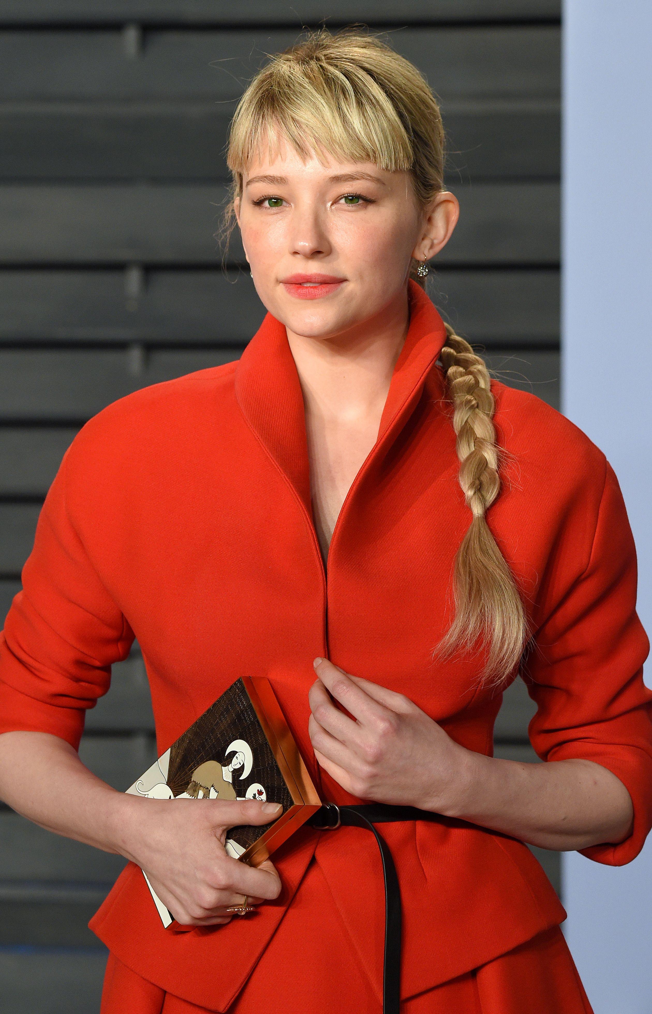 Mujer rubia con flequillo lacio y cabello atado en una trenza larga