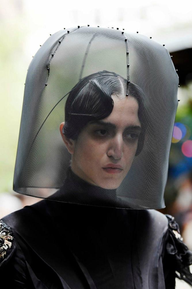 Hombre de cabello negro, peinado con gel, lleva una especie de gorro de apicultor, o sea que el rostro está cubierto por una redecilla negra