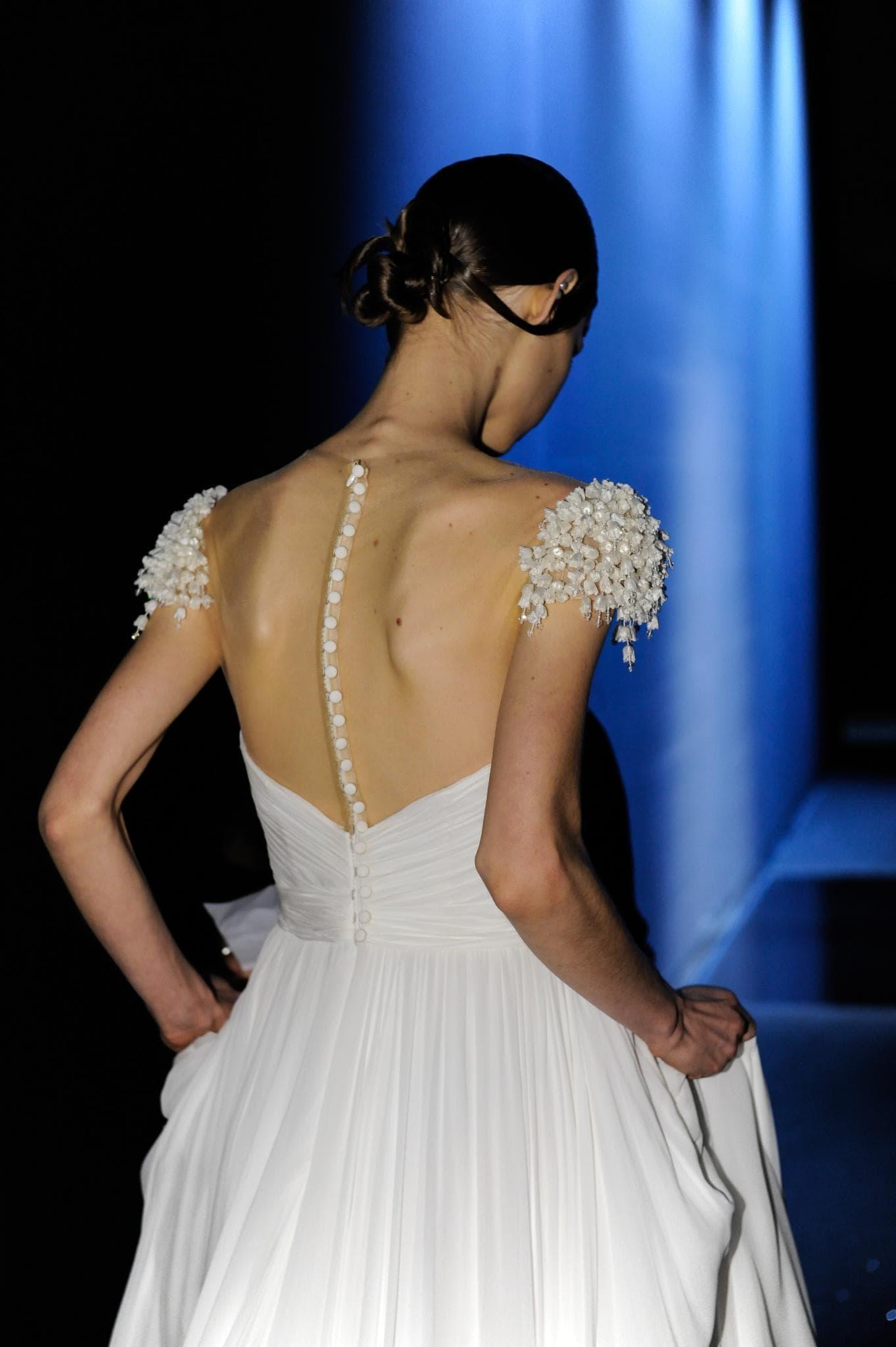 Vista de atrás de mujer castaña oscura con cabello recogido, parece estar vestida de novia