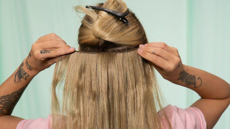 mujer rubia aplicando extensiones de pelo
