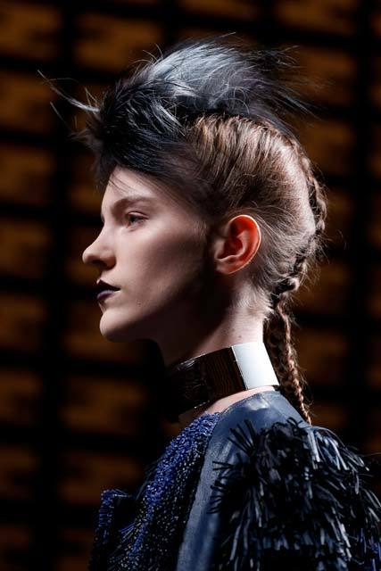 Vista de perfil de mujer de cabello castaño oscuro, recogido con trenza y aplique negro de plumas