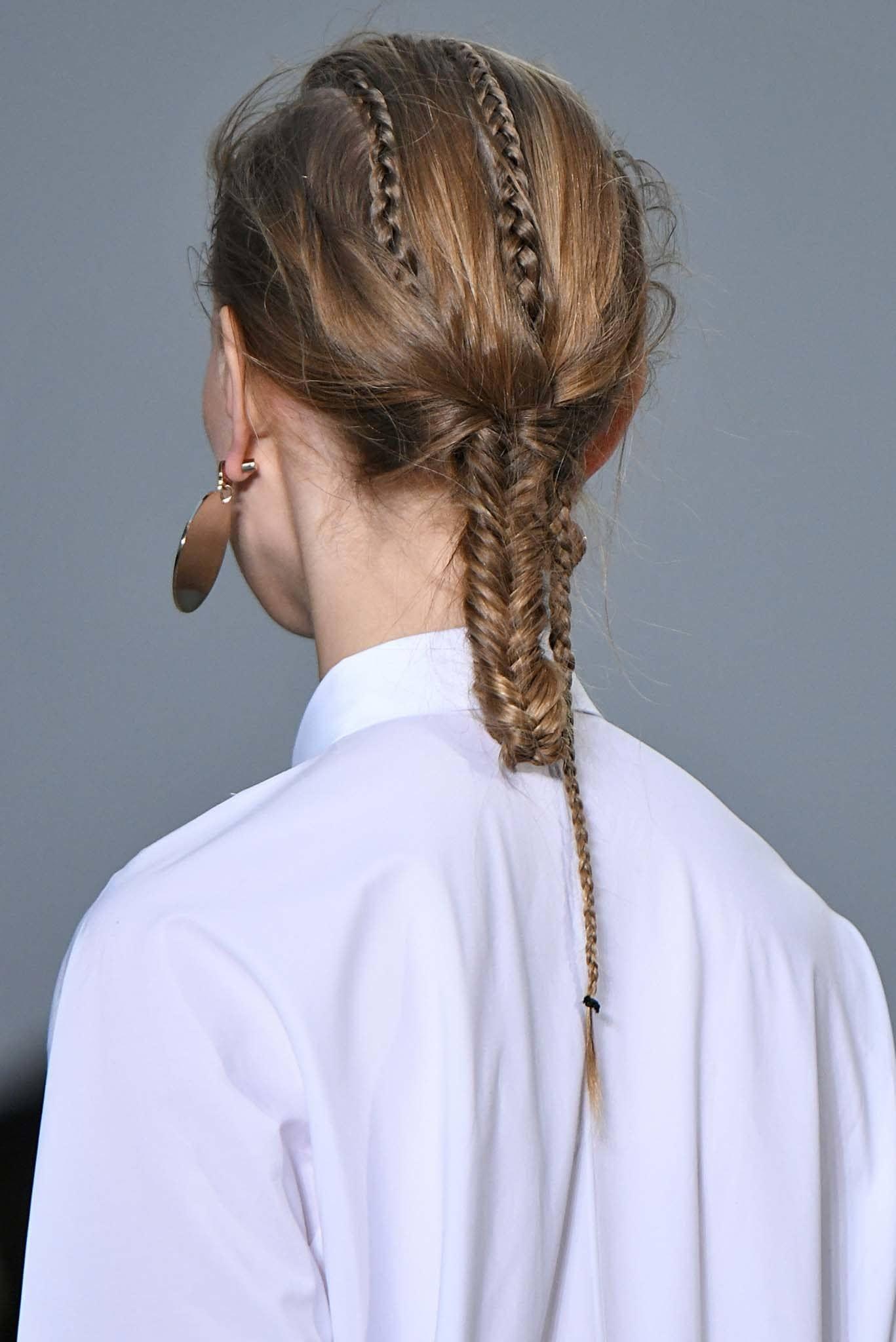 Vista de atrás de mujer castaña peinada con un recogido hecho con trenzas y cabello lacio