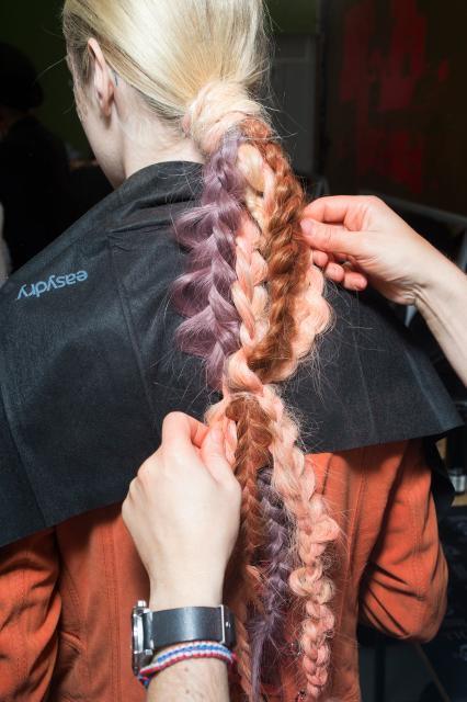 Vista de atrás de mujer rubia con una trenza hecha con mechones de diferentes colores (rosa, lila, colorado, etc.)