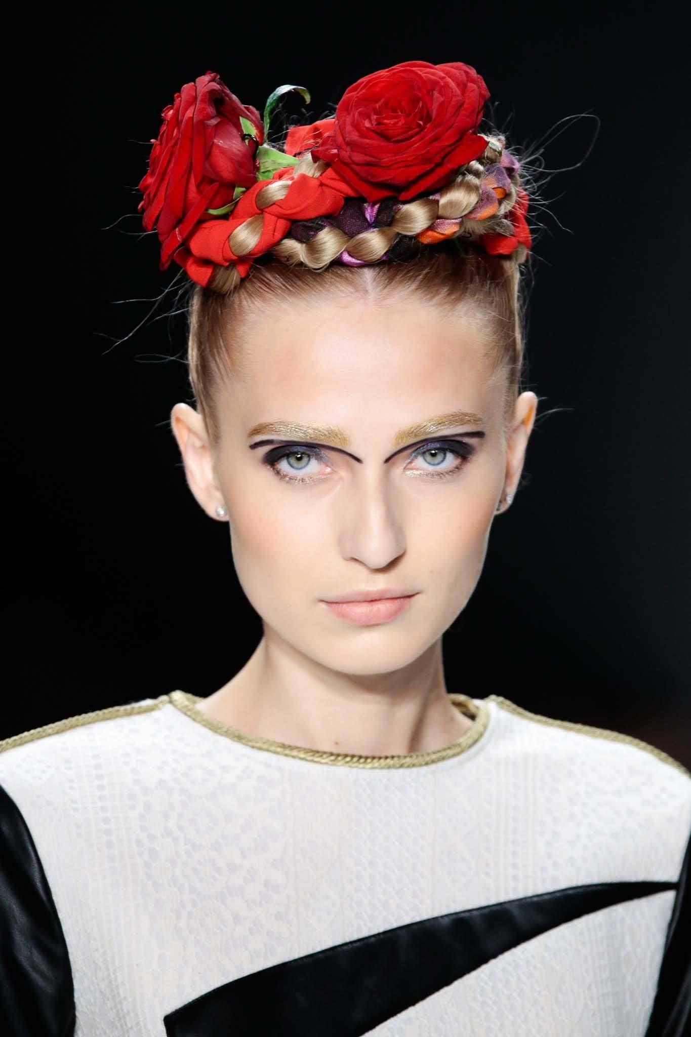 Mujer de cabello rubio peinado tirante hacia atrás con rodete formado por trenzas y rosas rojas