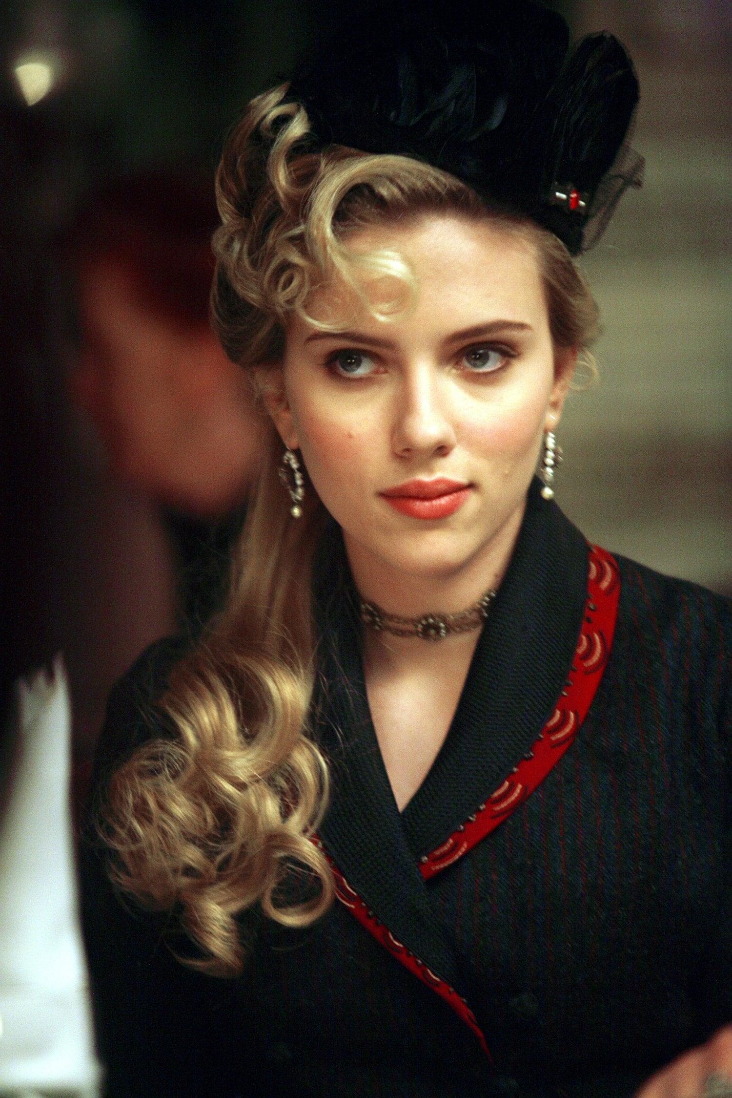 Scarlett Johansson peinada como de época, lleva la melena larga, lacia con rulos en la parte alta y en las puntas y un sombrero negro