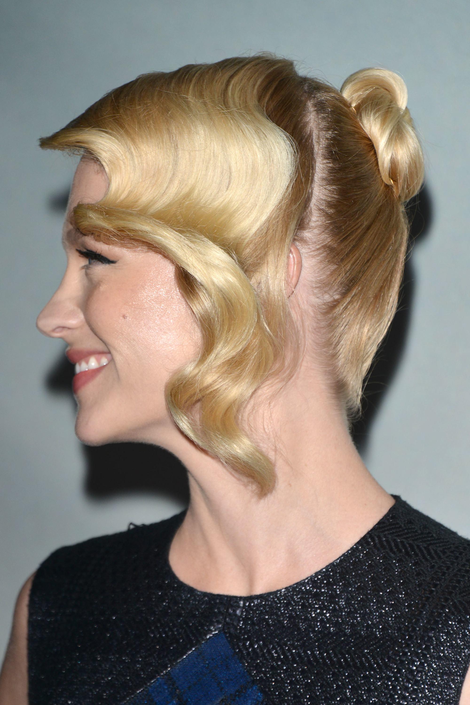 Mujer rubia de cabello atado, lleva los mechones delanteros con ondas y sueltos