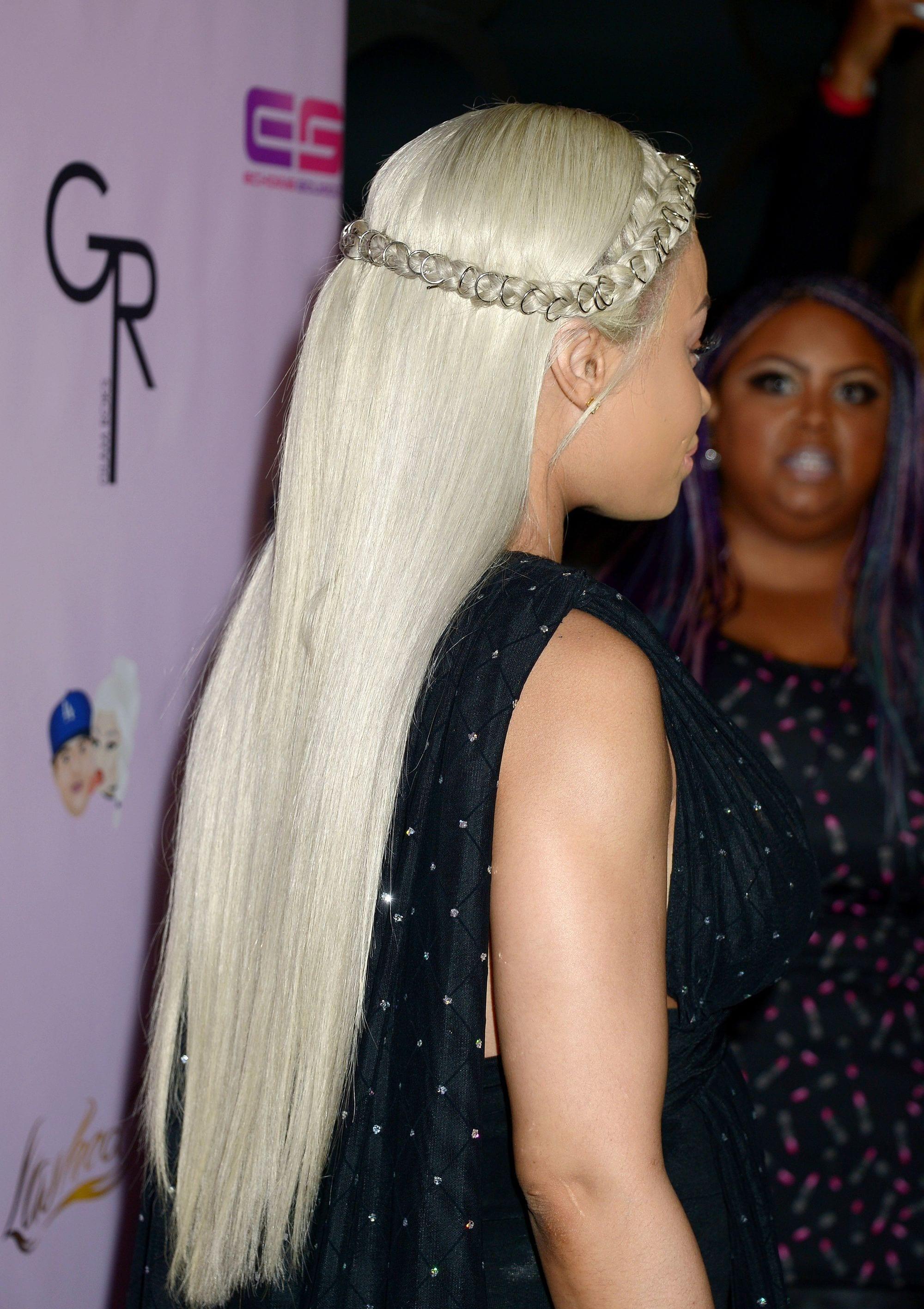 Mujer rubia de cabello platinado ultra lacio, sujeta con una vincha hecha de trenzas